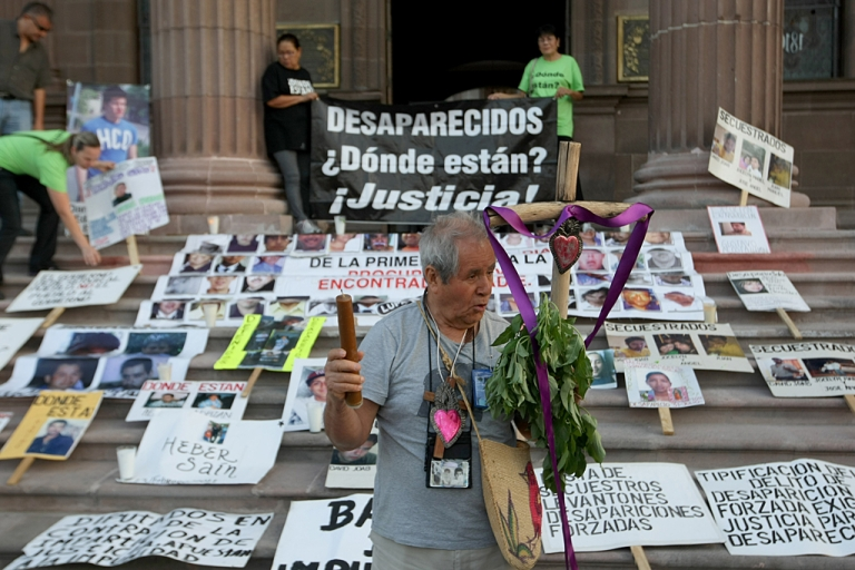 <p>A man who has a missing relative holds a cross and a sign during a protest demanding information on the whereabouts of missing relatives, during the commemoration of the International Day of the Disappeared in Monterrey, Mexico, on Aug. 30, 2012.</p>
