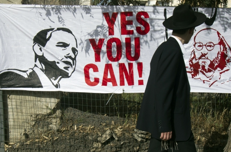 <p>An Orthodox Jewish man walks past a banner on March 13, 2013 in Jerusalem.</p>