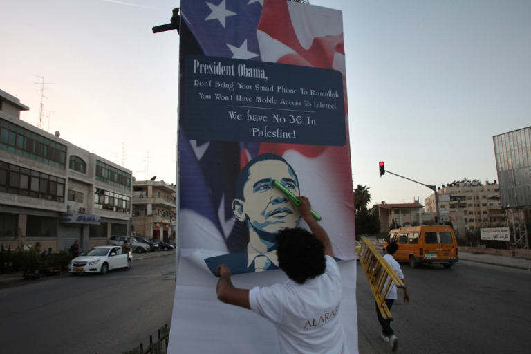 <p>A Palestinian activist hangs up an anti-Obama poster in the West Bank city of Ramallah on March 11, 2013. Many Palestinians have middling expectations for US President Barack Obama's three-day visit to Israel and the Palestinian territories, a trip that will begin on March 20.</p>