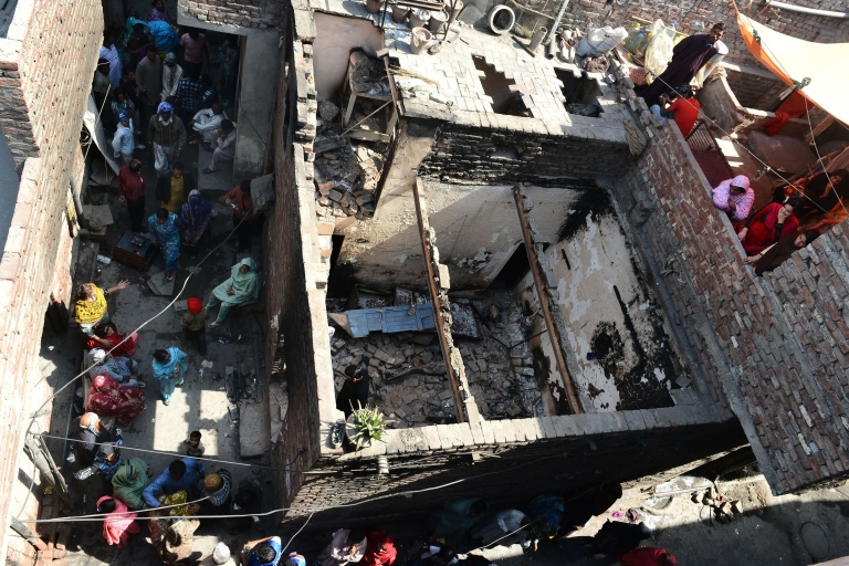 <p>Pakistani Christians gather around their burnt out homes torched by Muslim demonstrators in Lahore on March 10, 2013. Christians demonstrated around Pakistan to protest after a Muslim mob torched more than 100 Christian homes following allegations of blasphemy.</p>