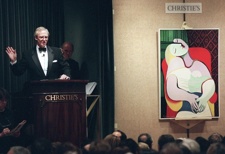<p>New York, UNITED STATES: File picture taken November 10, 1997 shows Christopher Burge, chairman of Christie's (L), starting the bidding for Pablo Picasso's painting, 'Le Reve' in New York at an auction of the collection of Victor and Sally Ganz.</p>