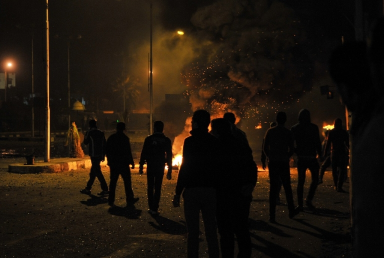 <p>Egyptian protesters stand near burning tyres outside the main security headquarters in the canal city of Port Said on March 5, 2013.</p>