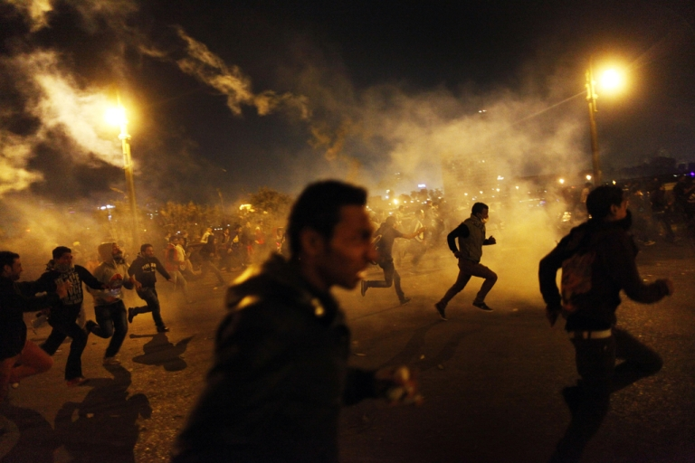 <p>Egyptian protesters run for cover from tear gas fired by riot police during clashes in Cairo, on March 8, 2013. Egyptian Interior Minister Mohamed Ibrahim sacked the riot police chief amid strikes by policemen who complained they are ill-equipped to confront protesters, state media reported.</p>