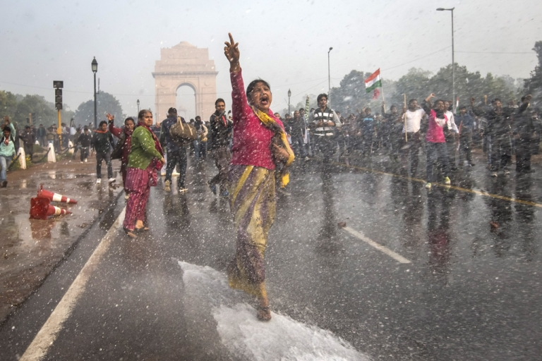 <p>A protester chants slogans as she braces herself against the spray fired from police water canons during a protest against the Indian government on Dec. 23, 2012, in New Delhi, India. Reaction to rape incidents around the globe have reinvigorated awareness, but the question of coverage in the news remains a thorny issue.</p>