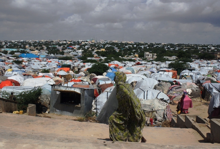 <p>A Somali refugee walks in front of a camp for internally displaced people near the Parliament in Mogadishu on Dec. 4, 2012.</p>