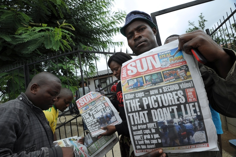 <p>A man shows the front page of a local newspaper with the shocking story about a Mozambican taxi driver who was dragged to his death behind a police van.</p>