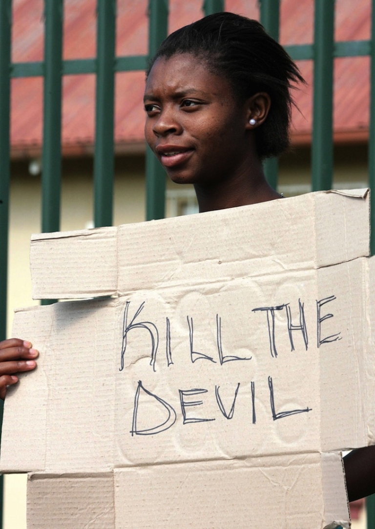 <p>An angry resident of the South African informal settlement Skielik stands with a placard during a protest outside the Swartruggens Magistrate's Court, west of Johannesburg 17 January 2008.</p>