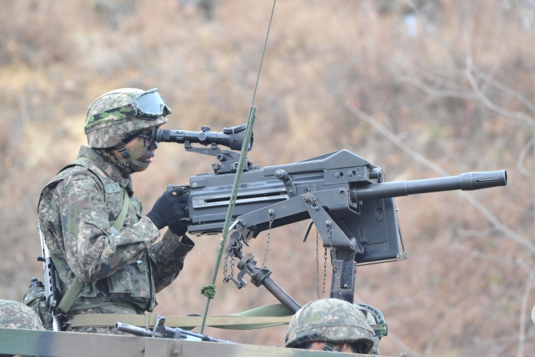 <p>A South Korean soldier looks through the scope of a K-4 automatic grenade launcher at a check point during a drill near border in Paju on March 28.</p>