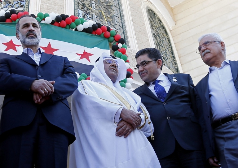 <p>Prime Minister of the interim government of Syria Ghassan Hitto (2R), head of the Syrian opposition delegation, Ahmed Moaz al-Khatib (L), and Syrian National Council (SNC) President George Sabra (R) at the inauguration of the first Syrian interim government embassy in Doha on March 27, 2013.</p>