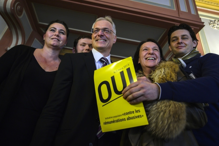 <p>Swiss businessman and senator Thomas Minder (3rdR) poses on March 3, 2013 with members of the support committee behind a poster reading 'Yes' in French while waiting for the result of a nationwide vote in Schaffhausen. Switzerland took part in a popular vote on whether to rein in executive pay and force business leaders to give up departure compensation known as golden parachutes.</p>