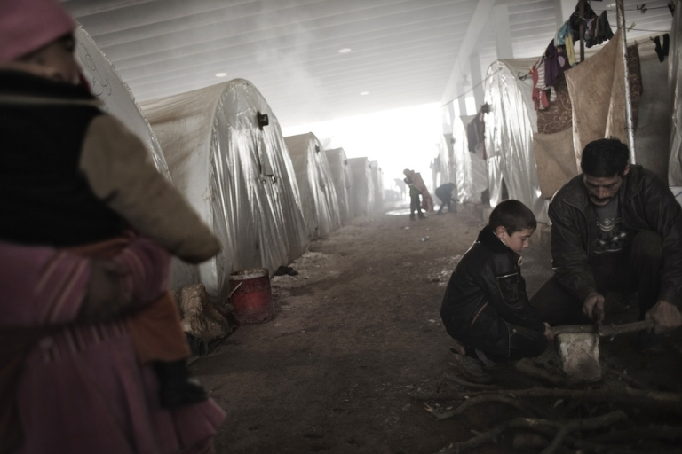 <p>A Syrian refugee child helps a man to cut wood at a refugee camp near the northern city of Azaz on the Syria-Turkey border, on Jan. 9, 2013.</p>