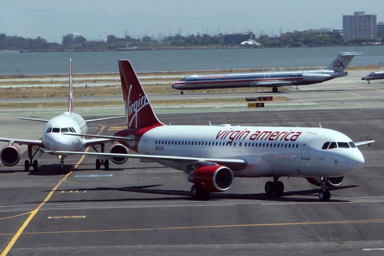 <p>Two Virgin America planes taxi on the runway after arriving at San Francisco International Airport on Aug. 8, 2007, in San Francisco, Calif. Earlier this week Virgin America and Singapore Airlines expanded their existing partnership to allow frequent flyers to earn and redeem points, or miles, for travel on either carrier.</p>