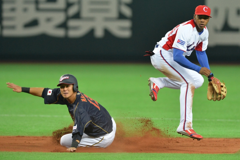 <p>Cuba's infielder Erisbel Arruebarruena (R) turns a double play as Japan's runner Sho Nakata (L) is forced out during the sixth inning of a first-round Pool A game in the World Baseball Classic tournament in Fukuoka, Japan, on March 6, 2013.</p>
