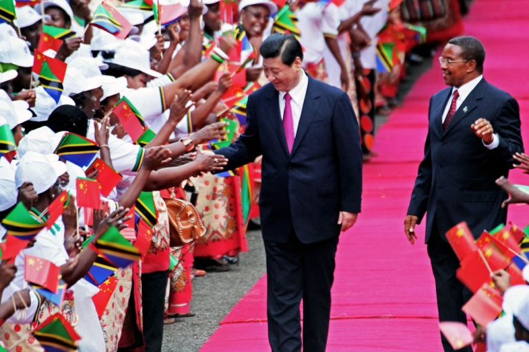<p>Chinese President Xi Jinping (L) shakes hands to members of a welcoming committee eyed by Tanzanian President Jakaya Kikwete upon his arrival at Julius Nyerere International airport in Dar es Salaam on March 24, 2013.  Xi Jinping and Peng Liyuan are on a two day visit to Tanzania, their first stop in Africa as part of an international trip.</p>