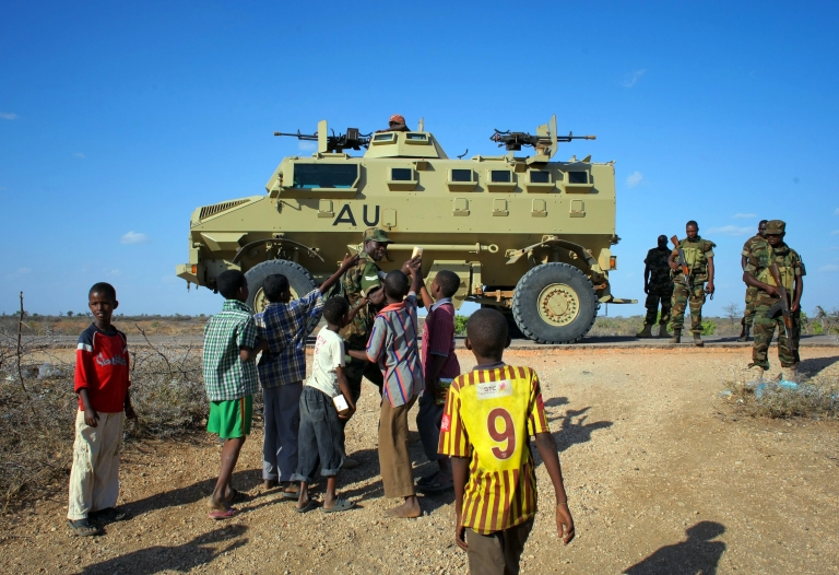 <p>A handout picture taken and released by the African Union-United Nations Information Support team on February 28, 2013 shows a Ugandan soldier serving with the African Union Mission in Somalia (AMISOM) handing out biscuits to young Somali children.</p>