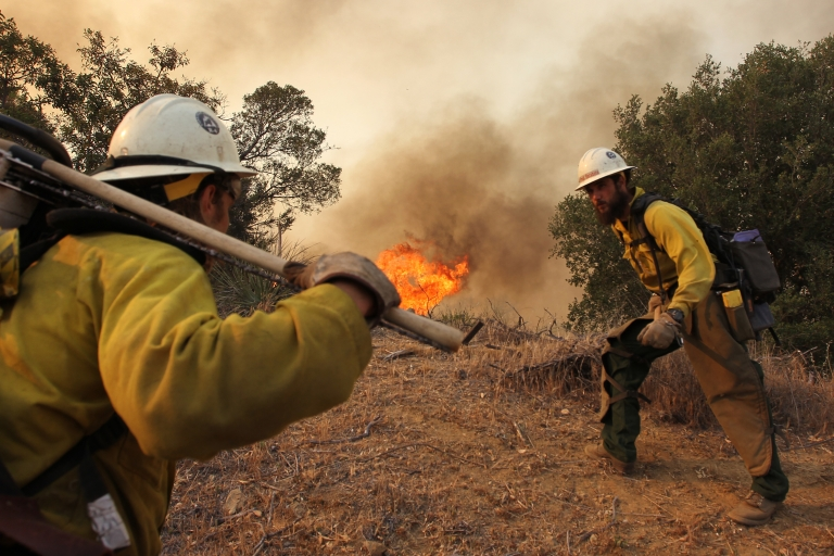 <p>Firefighters with the Type 1 Interagency Hotshot Crew (IHC), based out of the Lone Peak Conservation Center, in Draper, Utah, build a fire break as the Springs fire continues to grow on May 3, 2013 near Camarillo, California. Natural disasters like this may increase with worsening climate change say scientists. A new study has shown that nearly all scientists believe that climate change is man made.</p>