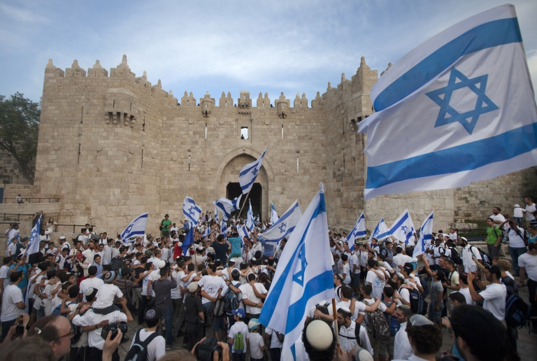 <p>Israeli youths hold their national flag as they take part in the 'flag march' through Damascus Gate in Jerusalem's old city during celebrations for Jerusalem Day on May 8, 2013 which marks the anniversary of the 'reunification' of the holy city after Israel captured the Arab eastern sector from Jordan during the 1967 Six-Day War.</p>
