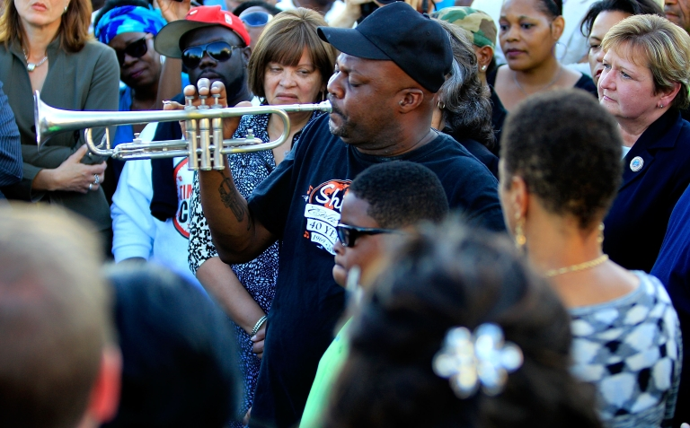 <p>Kenneth Terry with the Treme Brass Band plays the trumpet on the cornor of North Villere and Frenchmen Street during a community response to a shooting during a Mother's Day parade, on May 13, 2013 in New Orleans, Louisiana. Nineteen people were injured during the shooting, including two children.</p>