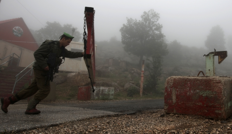<p>An Israeli soldier partially closes a barrier across a road, on Mount Hermon in the northern Israel occupied Golan Heights on May 15, 2013, after two projectiles fired from Syria hit Mount Hermon.</p>