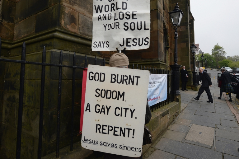 <p>A protestor stands outside the entrance to the Church of Scotland General Assembly on May 20,2013 in Edinburgh, Scotland. Members will be discussing whether to allow people in same sex relationships to be ordained as Ministers in the Church of Scotland.</p>