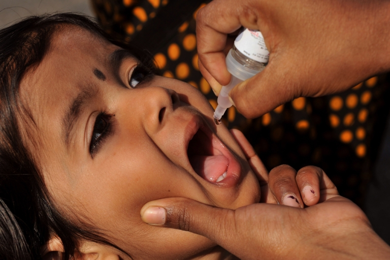 <p>An Indian medical volunteer administers a dose of oral vaccine to a child during a national immunisation programme in Hyderabad on February 19, 2012.</p>
