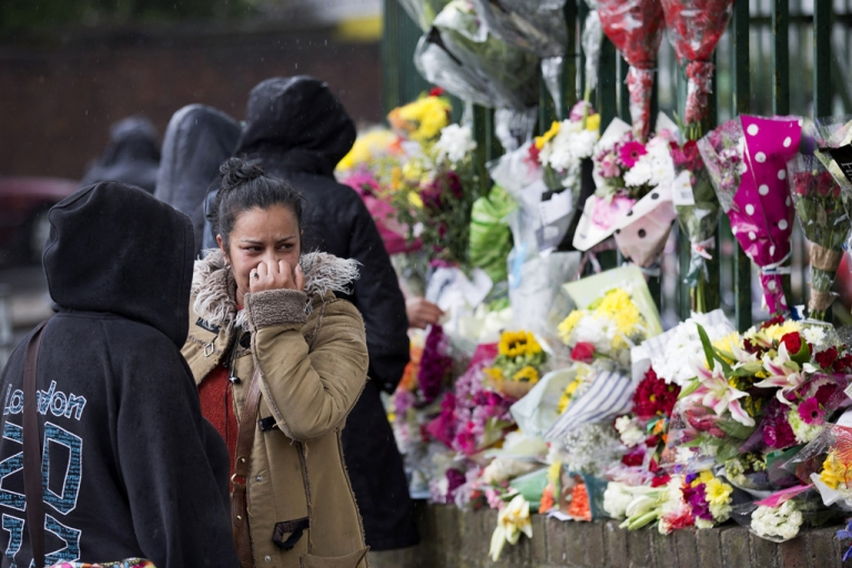 <p>A woman reacts as she looks at floral tributes left at the scene where Drummer Lee Rigby of the 2nd Battalion was killed outside Woolwich Barracks in London on May 24, 2013.</p>