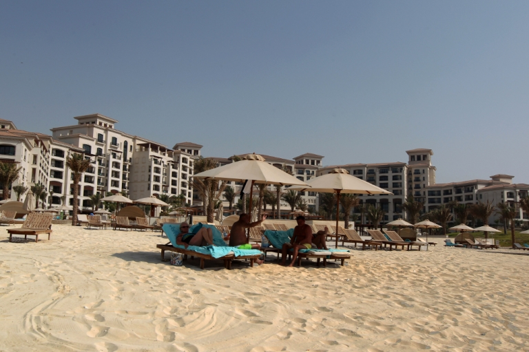 <p>Tourists sunbath along the beach at the St. Regis hotel located in the Saadiyat district, an Island off the city of Abu Dhabi on June 7, 2012.</p>