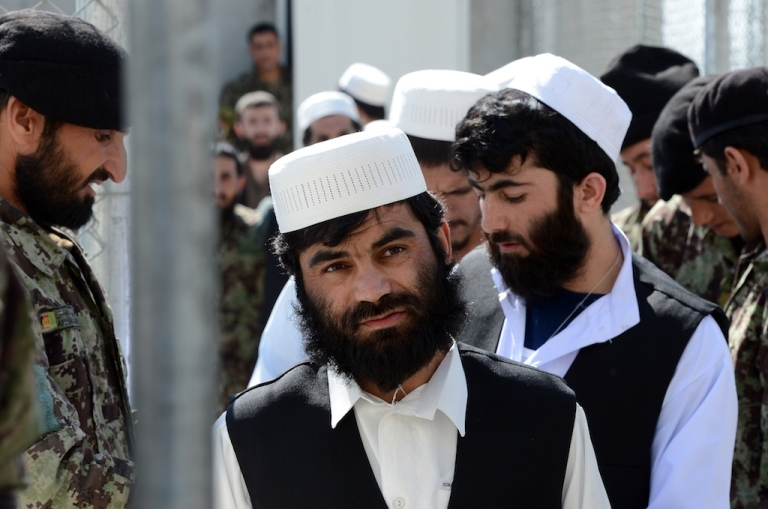 <p>Afghan detainees wait to be released during a ceremony to hand over Bagram prison to the Afghanistan government at Bagram Prison facilities on March 25, 2012.</p>