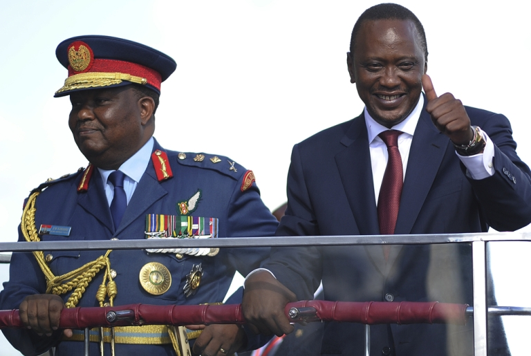 <p>Kenya's fourth President Uhuru Kenyatta (R) gives the thumbs up after being sworn-in April 9, 2013 in Nairobi. He is also facing trial on charges of crimes against humanity.</p>