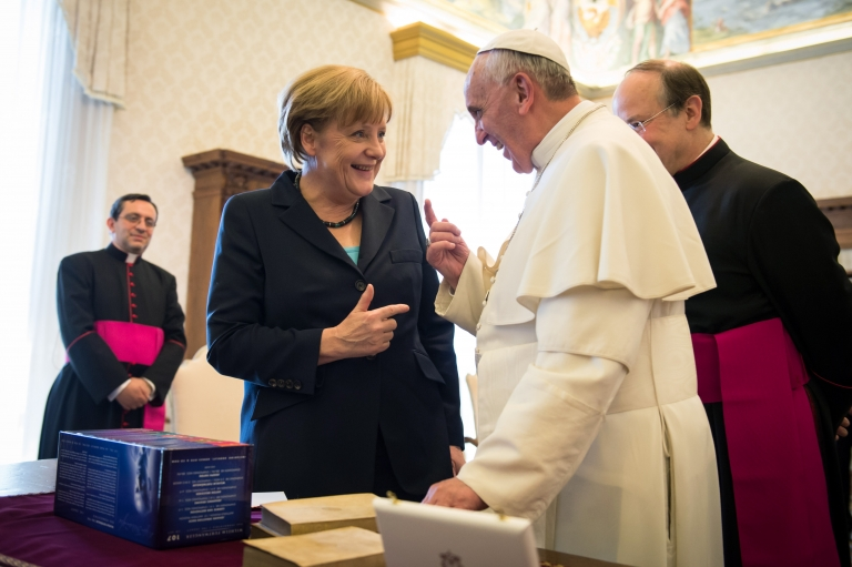 <p>Chancellor of Germany Angela Merkel and Pope Francis exchanges gifts after their meeting in his private library at the Vatican on May 18, 2013 in Vatican City, Vatican.</p>