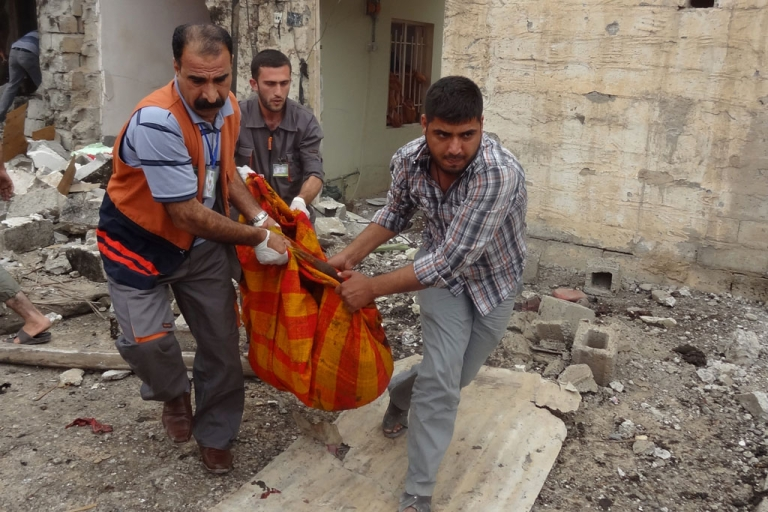 <p>Iraqis carry a bombing victim in the northern city of Kirkuk on May 15, 2013. Bombings in Iraq, including two car bomb in Kirkuk, killed several people and wounded many more, security and medical officials said.</p>