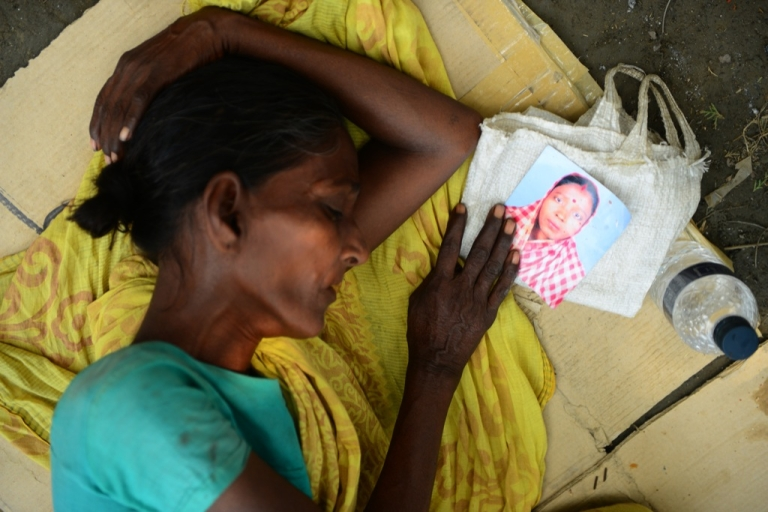 <p>A Bangladeshi woman sleeps as she holds the portrait of her missing relative, believed to be trapped in the rubble of an eight-storey building collapse in Savar, on the outskirts of Dhaka, on May 4, 2013.</p>