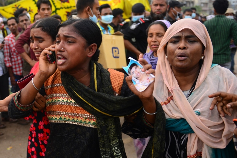 <p>A Bangladeshi woman uses her cell phone as she holds a portrait of her missing sister, believed trapped in the rubble 60 hours after an eight-storey building collapsed in Savar, on the outskirts of Dhaka, on April 26, 2013.</p>