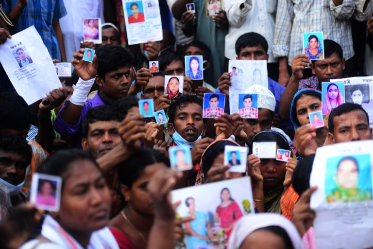 <p>Bangladeshi relatives hold photos of the missing and dead workers three days after an eight-storey building collapsed in Savar, on the outskirts of Dhaka on April 27, 2013. The death toll from the disaster had risen above 1,000 by May 10.</p>