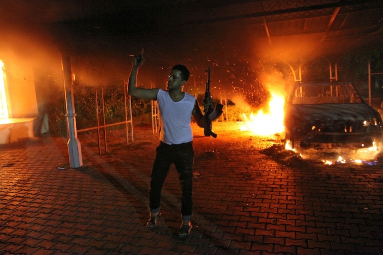 <p>An armed man waves his rifle as buildings and cars are engulfed in flames after being set on fire inside the US consulate compound in Benghazi late on Sept. 11, 2012.</p>