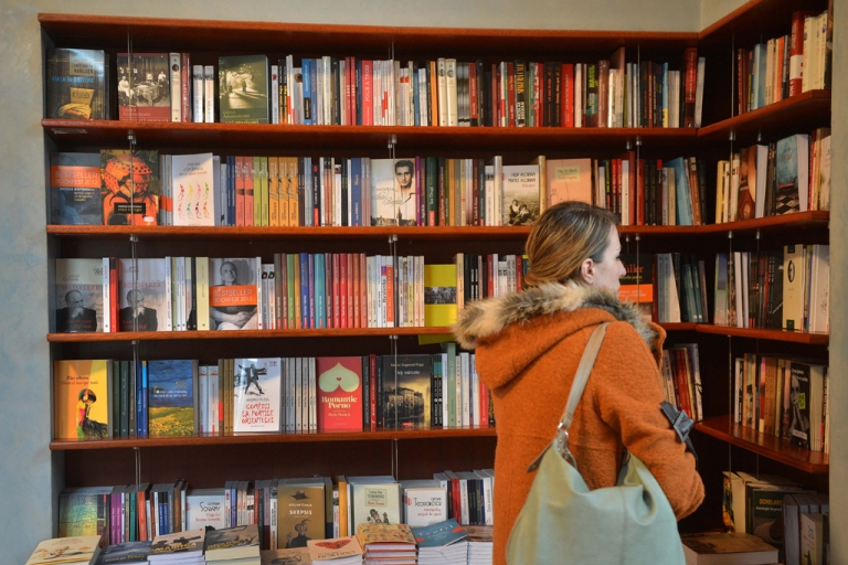 <p>A woman looks at the contemporary Romanian literature bookshelf at a library in Bucharest.</p>