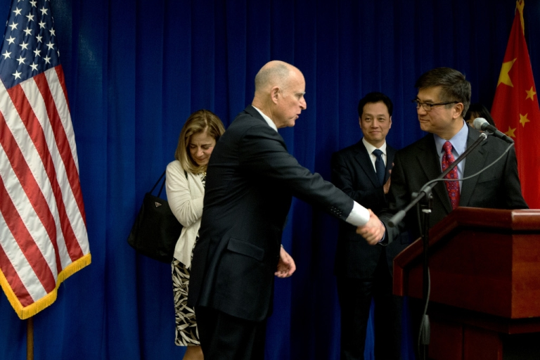 <p>US Ambassador to China Gary Locke shakes hands with California Governor Jerry Brown as Chinese Vice Minister of Commerce Wang Chao looks on during a Trade and Investment reception at the US Embassy on April 10, 2013 in Beijing.</p>