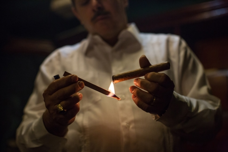 <p>Reynaldo Gonzalez, a demigod in the cigar realm, lights a Habano delicately with a cedar strip, which is said to preserve the rich flavor of a Cuban cigar.</p>