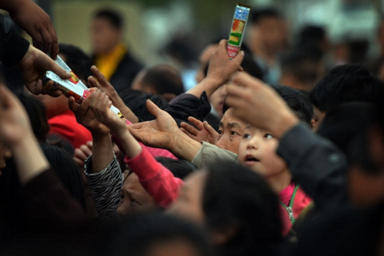 <p>Residents reach for food handouts after a magnitude 7.0 earthquake hit Lushan, Sichuan Province on April 21, 2013.</p>
