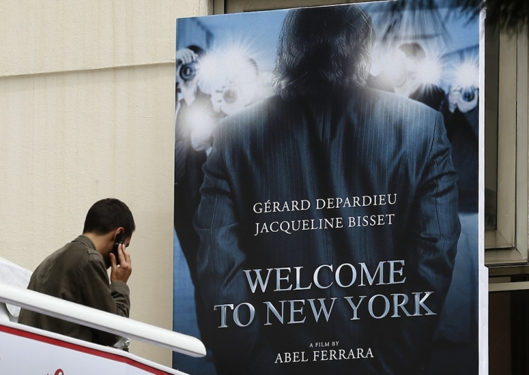 <p>A man speaks on the phone near the poster of the movie inspired by the story of former IMF chief Dominique Strauss-Kahn (DSK), 'Welcome to New York,' directed by Abel Ferrara and starring French actor Gerard Depardieu and British actress Jacqueline Bisset on May 16, 2013 during the 66th edition of the Cannes Film Festival in Cannes.</p>
