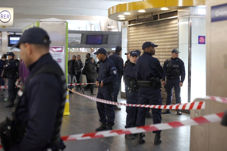 <p>Police officers stand at the site where a man armed with a box cutter attacked a French soldier patrolling a subway station of Paris' business district, stabbing him in the neck, on May 25, 2013 in La Defense. The soldier in uniform was armed and was patrolling as part of France's Vigipirate anti-terrorist surveillance scheme.  France's defense minister said the soldier stabbed in Paris Saturday was targeted because he was in the army and vowed to continue his country's