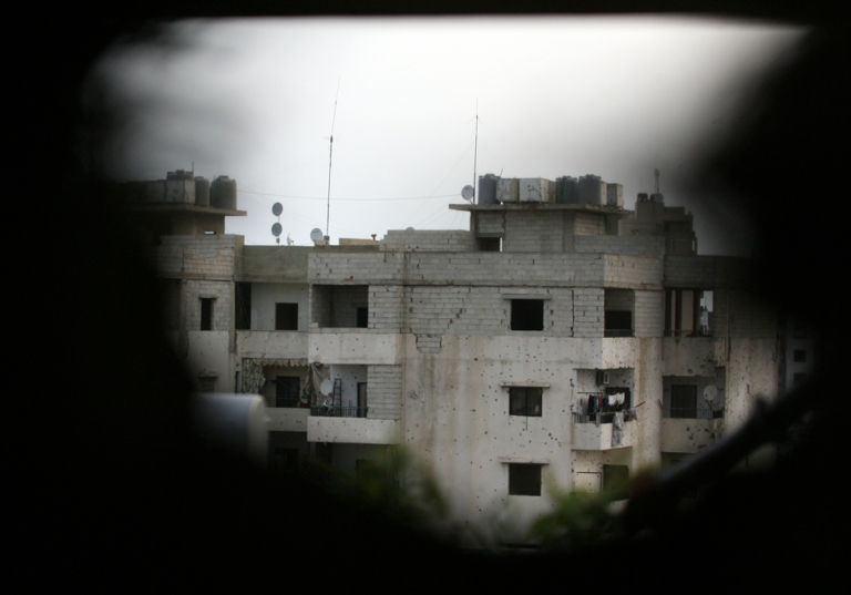 <p>A damaged building is seen through a hole in a wall in the Sunni district of Bab al-Tabbaneh following clashes with the Alawite neighbourhood of Jabal Mohsen in the Lebanese port city of Tripoli.</p>