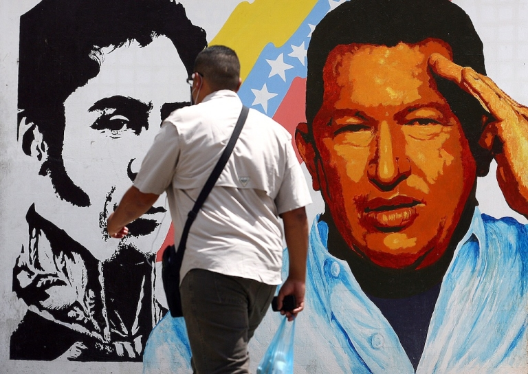 <p>A man walks past a mural portraying the Venezuelan flag, President Hugo Chavez and South American liberator Simon Bolivar at the 23 de Enero neighbourhood, in Caracas on March 5, 2013.</p>