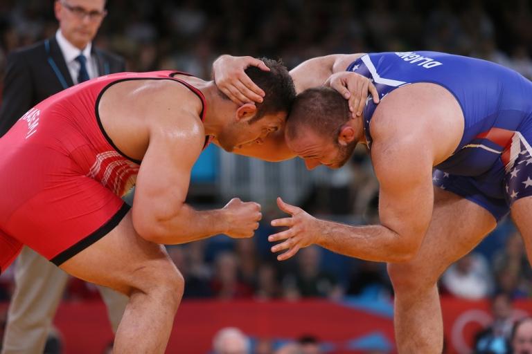 <p>Iran's Komeil Ghasemi, left, wrestles American Tervel Ivaylov Dlagnev in their men's 120-kg freestyle wrestling bronze-medal match on August 11, 2012 at the London Olympics.</p>