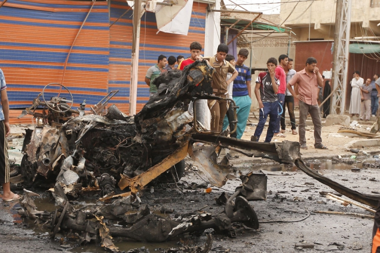 <p>Iraqis look at the remains of a car bomb that detonated in the Kamaliya area of eastern Baghdad on May 20, 2013. A wave of 12 bomb attacks across Iraq killed at least 15 people and wounded dozens more, security and medical officials said.</p>
