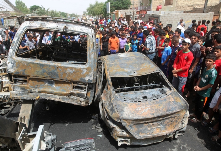 <p>Iraqis gather around burnt vehicles at the site of a car bombing at a market in Baghdad's impoverished district of Sadr City on May 16, 2013 as at least eight people were killed in blasts across the country. Violence in Iraq has fallen from its peak in 2006 and 2007, but attacks remain common, killing more than 200 people in each of the first four months of this year.</p>