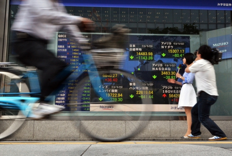 <p>A television journalist reports on the sharp fall in Japanese stocks on May 23, 2013.</p>