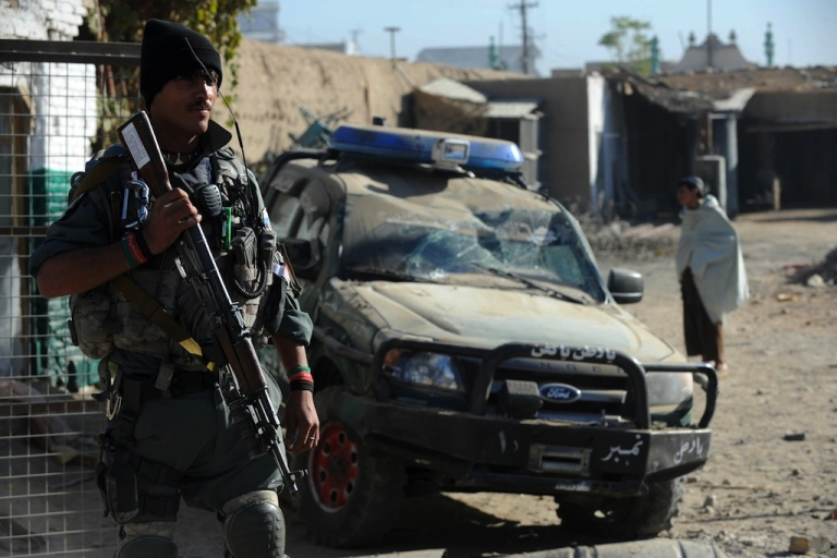 <p>An Afghan policeman keeps watch at the site of a suicide bomb attack in Kandahar on Nov. 8, 2012.</p>