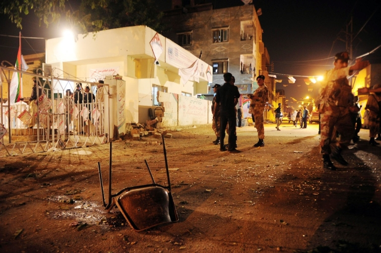 <p>Pakistani security officials stand guard at the site of twin bomb blasts near the secular Muttahida Qaumi Movement (MQM) party office in Karachi on May 4, 2013. Three people were killed and more than 20 others wounded in the blasts near the local party office, police said, ahead of next week's historic elections.</p>