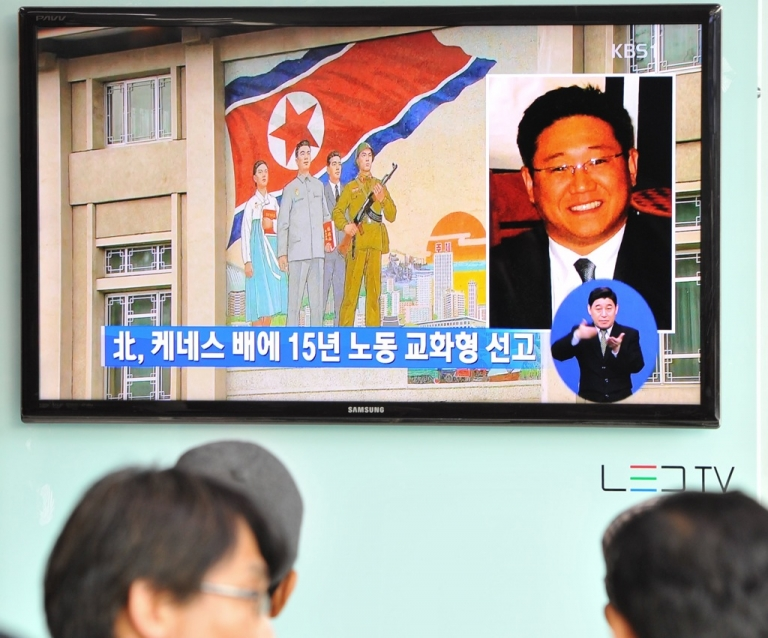 <p>Passersby watch a local television broadcast in Seoul on May 2, 2013 showing a picture of Kenneth Bae (R), a Korean-American tour operator detained in North Korea. North Korea said on May 2 it had sentenced Bae to 15 years' hard labor for 'hostile acts', stoking tensions with the United States.</p>
